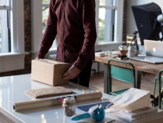 man holding a package on a desk